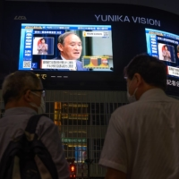 Pedestrians stop to watch a screen broadcasting a news conference by Prime Minister Yoshihide Suga in Tokyo on Thursday.   BLOOMBERG