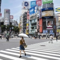 A woman protects herself from the sun and the heat with an umbrella as she crosses a street in Tokyo on Monday. | AFP-JIJI