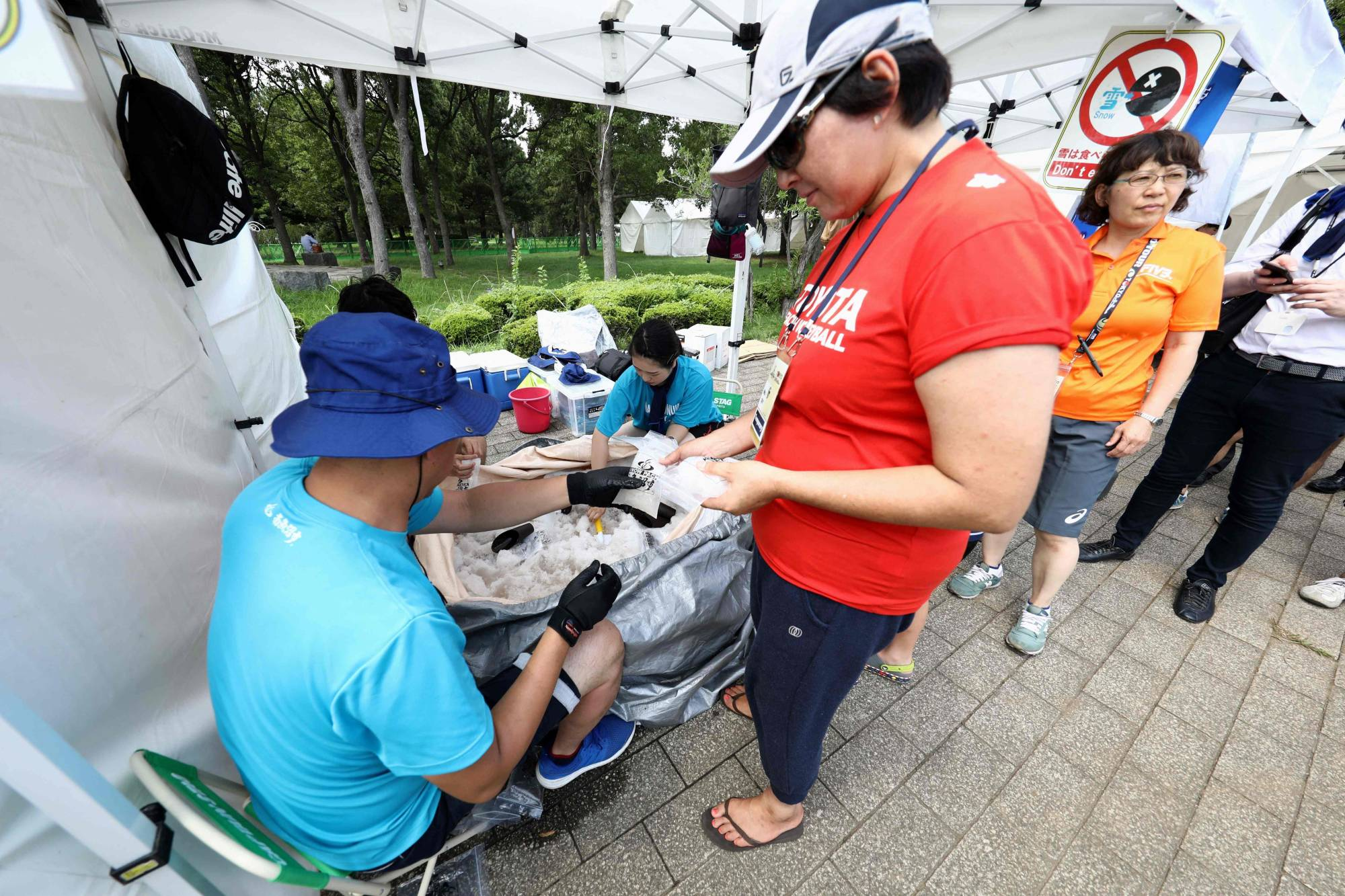 People receive ice packs to cool off during a beach volleyball test event for the Tokyo Olympics at Shiokaze Park in the capital in July 2019. | AFP-JIJI