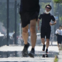 Runners jog on a sidewalk around the Imperial Palace during a heat wave in Tokyo last August. | AFP-JIJI