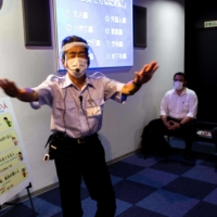 A Japanese staff member instructs a group of residents during a disaster simulation course at the Ikebukuro Life Safety Learning Center in Tokyo on June 14.    AFP-JIJI