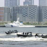 The Japan Coast Guard conducts a drill to simulate a response to a suspicious boat in waters off the Tokyo Games' athletes village on Tuesday, the same day the village officially opened. | KYODO