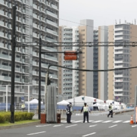 Security guards seal off the athletes village for the Tokyo Games on Tuesday. | KYODO