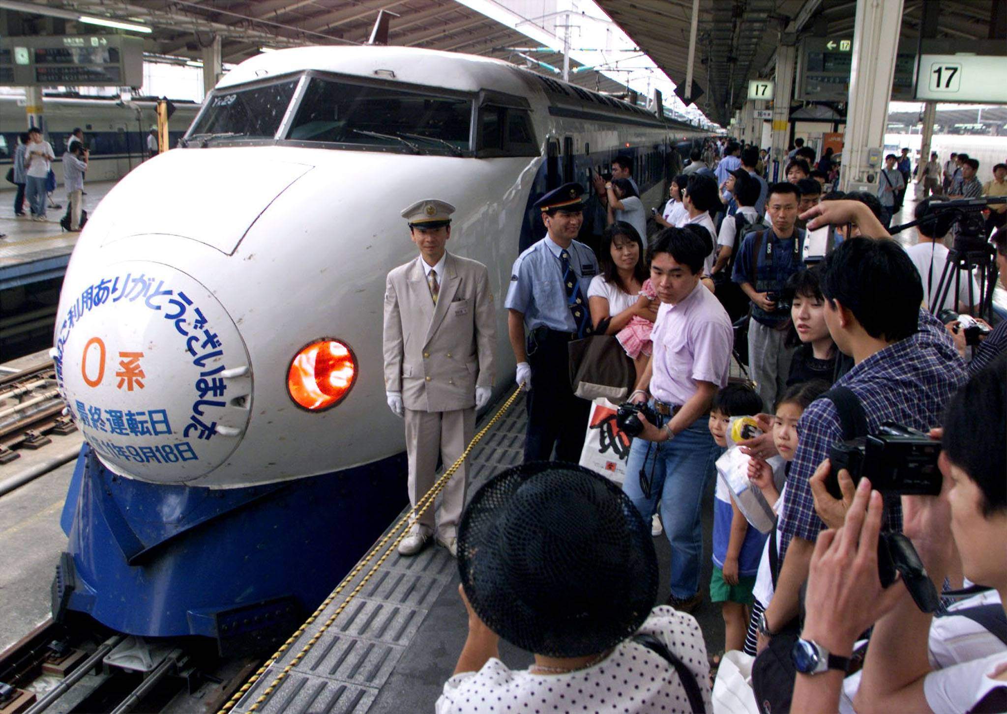 Train fans crowd around an original Zero bullet train model at Tokyo Station. The shinkansen started its run in 1964, the year of Tokyo Olympics. | REUTERS