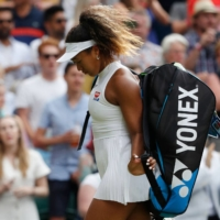 Japan's Naomi Osaka leaves the court after being knocked out of the Wimbledon tournament in the first round in July 2019. | AFP-JIJI