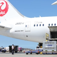 Workers unload AstraZeneca vaccines, shipped from Japan, from an airplane at Taoyuan International Airport in Taiwan on July 8. | TAIWAN CENTERS FOR DISEASE CONTROL / VIA REUTERS