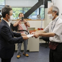 Lawyer Shuichi Adachi (right), representing a citizens' group, submits a letter to a Hiroshima Prefectural Government official Monday at the prefectural government building asking for International Olympic Committee chief Thomas Bach's visit to Hiroshima to be canceled. | KYODO