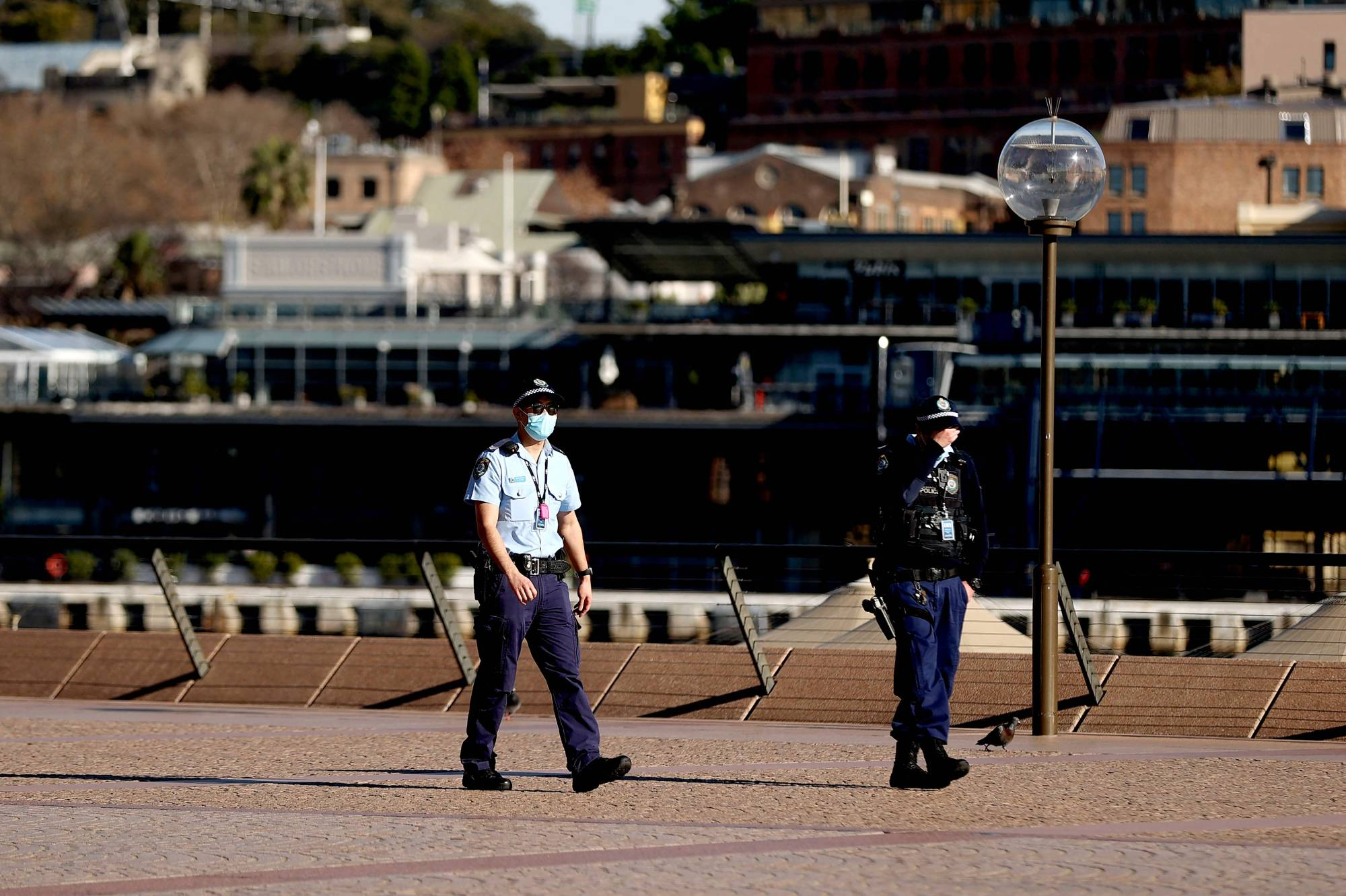 Police officers patrol around the Opera House on Tuesday as Sydney's 5 million residents prepare for 'at least' another two weeks of COVID-19 lockdown.   AFP-JIJI