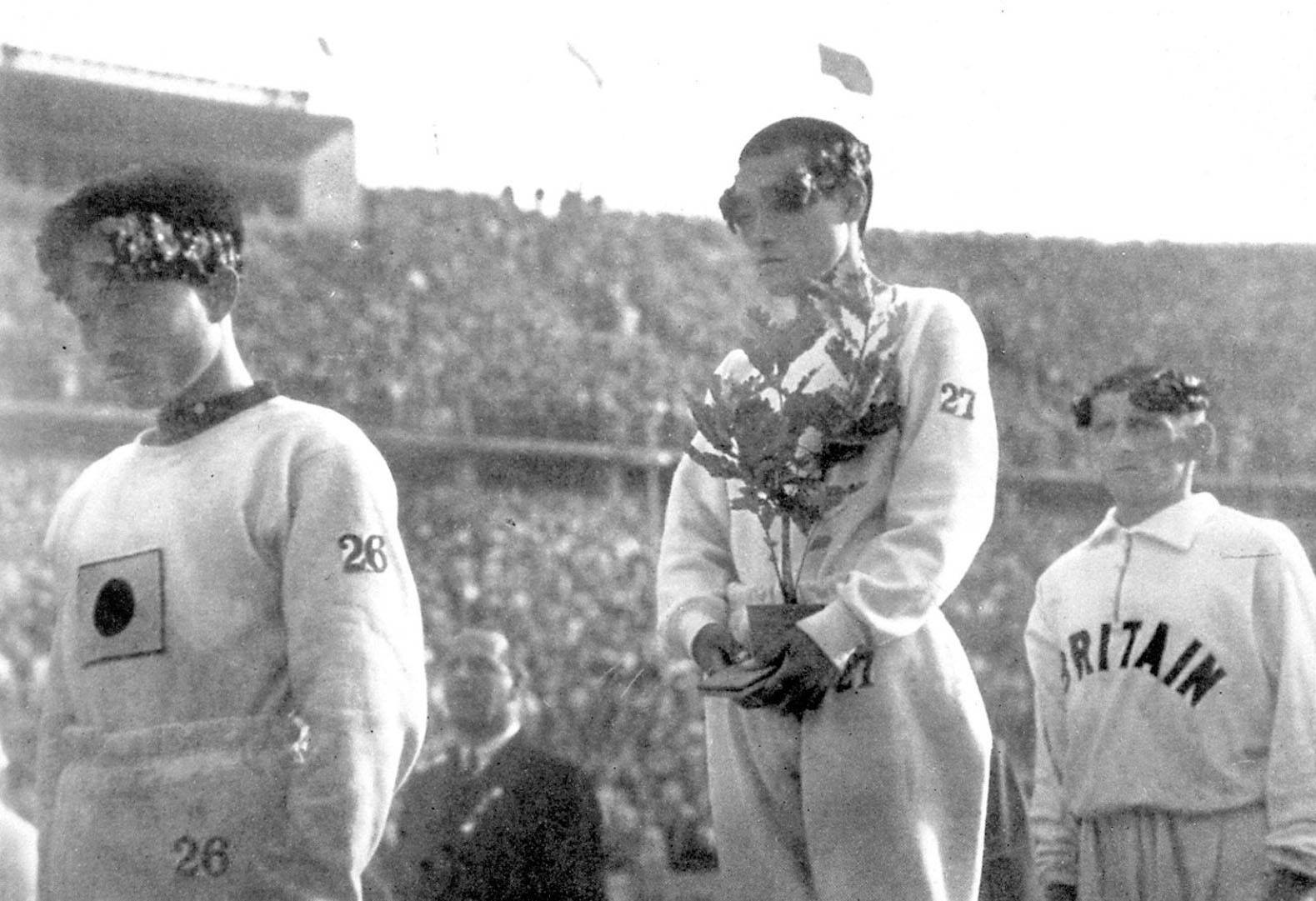 The gold medalist in the marathon at the 1936 Berlin Games, Sohn Kee-chung, stands on the podium with his head lowered instead of looking at Japan's Rising Sun flag.   KYODO