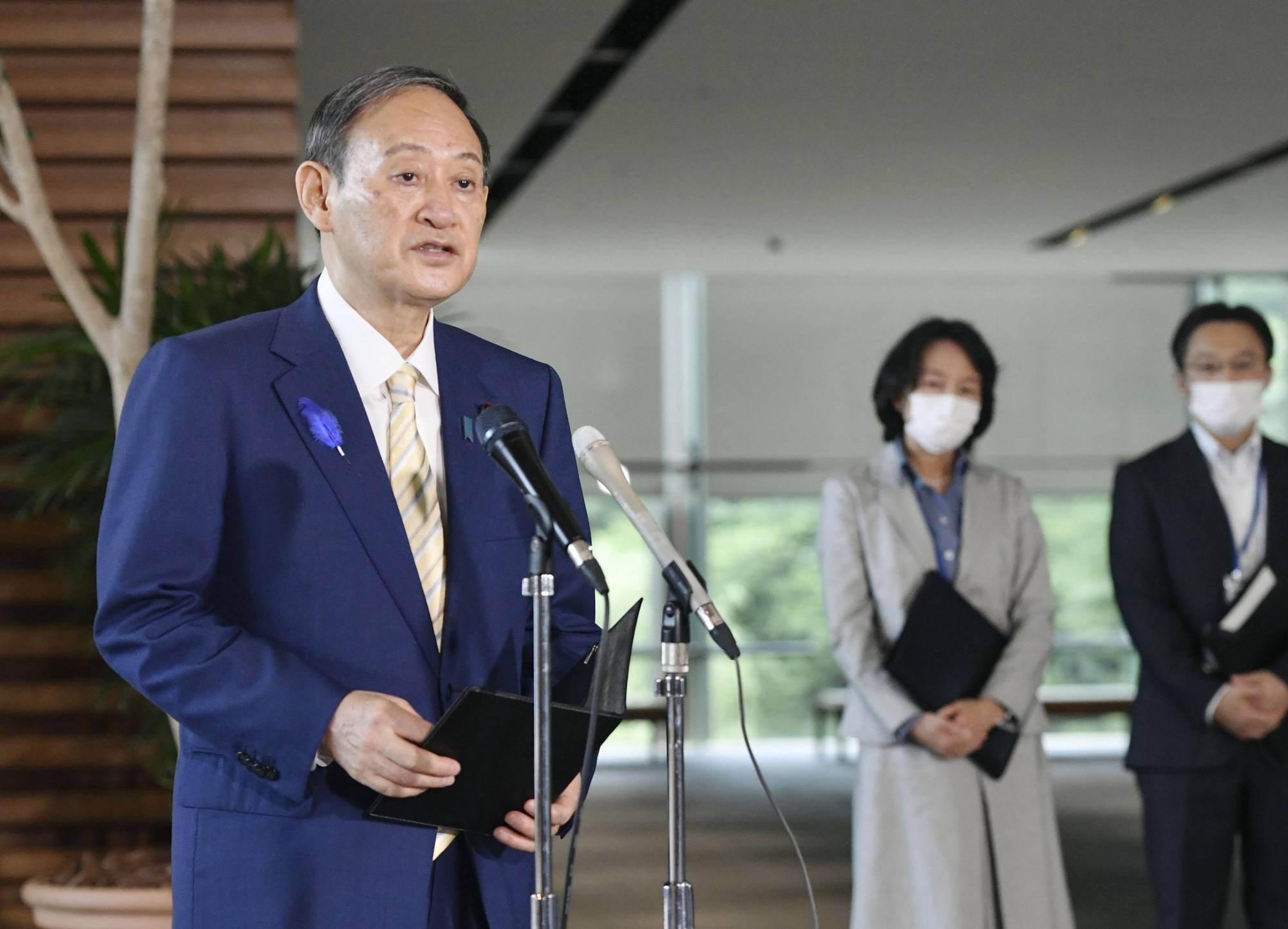 Prime Minister Yoshihide Suga speaks to reporters in Tokyo on Wednesday. | KYODO