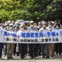 Plaintiffs who claim they should receive the same benefits as those provided for atomic bomb survivors walk to the Hiroshima High Court on Wednesday. | KYODO