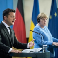 Ukrainian President Volodymyr Zelenskiy and the German Chancellor Angela Merkel give statements ahead of talks at the Chancellery in Berlin on Monday.  | POOL VIA / REUTERS