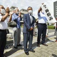 Masaaki Takano (center) and other plaintiffs who claim they should receive the same benefits as those provided to atomic bomb survivors applaud in front of the Hiroshima High Court on Wednesday after the court ruled in their favor.  | KYODO
