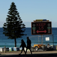 A COVID-19 health notice is displayed at Bondi Beach in Sydney. | BLOOMBERG
