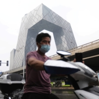 A man rides on a scooter past the China Central Television headquarters in Beijing on Tuesday. Assuming that global emissions reach a peak around 2040, Beijing would experience an average temperature increase of 2.2 C to 2.4 C.   REUTERS