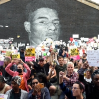 Demonstrators gather in front of a Marcus Rashford mural in Withington, Manchester, on Tuesday, after it was defaced following the Euro 2020 final. | REUTERS