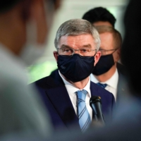 International Olympic Committee President Thomas Bach speaks to the media after meeting Prime Minister Yoshihide Suga in Tokyo on Wednesday. | POOL / VIA AFP
