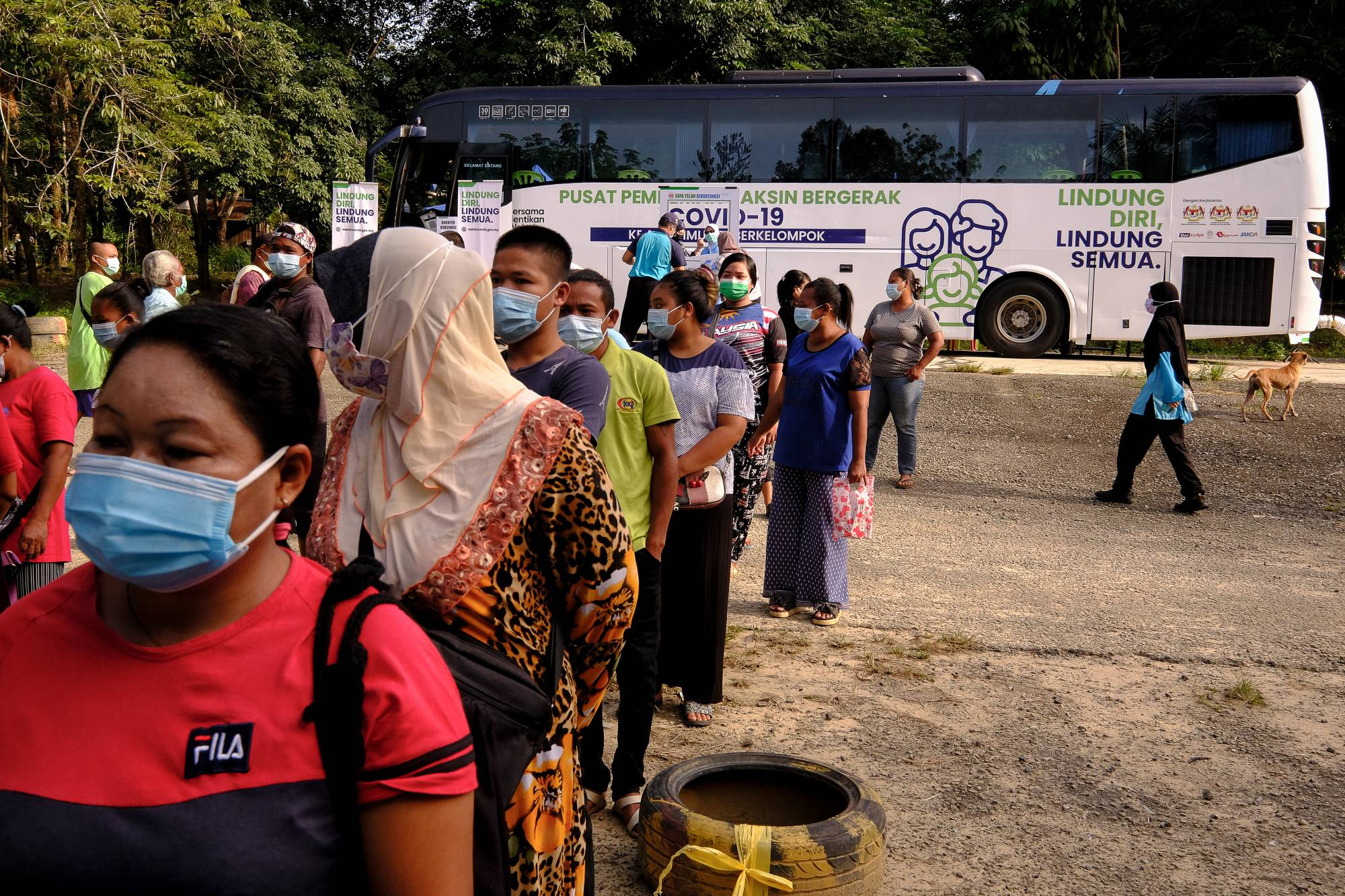Residents wait in line to register for the Pfizer-BioNTech COVID-19 vaccine at a mobile vaccination clinic set up in Kuala Langat, Malaysia, on Thursday. | BLOOMBERG