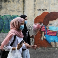 Women walk past a mural in Kuala Lumpur in September 2020. Although Malaysian women can apply for citizenship for children born overseas, decisions often take years and rejections are common. | REUTERS