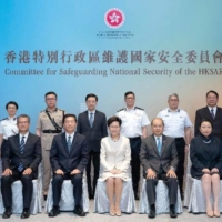 Carrie Lam (center), flanked by Security Secretary Chris Tang (standing third from right), Immigration Director Au Ka-wang (standing second right) and Customs Commissioner Hermes Tang (standing second left) pose for a photo in July 2020. | BLOOMBERG