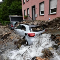 Water runs past a house and a car covered in rubble after heavy rain and floods caused major damage in Hagen, Germany, on Thursday. | AFP-JIJI