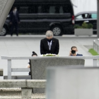 International Olympic Committee chief Thomas Bach observes a moment of silence after laying a wreath Friday at a cenotaph dedicated to atomic bomb victims in the Peace Memorial Park in Hiroshima. | KYODO