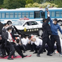The Metropolitan Police Department officers hold a VIP protection drill in Tokyo in June to prepare for the Tokyo Olympics. | KYODO