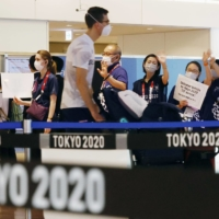Officials wait for foreign athletes arriving at Tokyo's Haneda Airport on Thursday. | KYODO