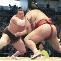 Hakuho (left) defeats Takayasu on the 13th day of the Nagoya Grand Sumo Tournament at Dolphins Arena in Nagoya on Friday.    KYODO