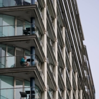 A lone man sits on an apartment building balcony at Circular Quay during a lockdown to curb the spread of COVID-19 in Sydney on Thursday. | REUTERS