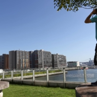 A man uses binoculars to look at the Athletes Village, where two athletes have tested positive for COVID-19, ahead of Tokyo 2020 Olympic Games, on Saturday. | REUTERS