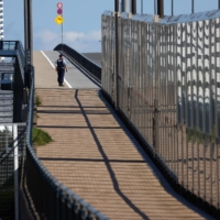 A police officer patrols the area outside the Athletes Village, where two athletes have tested positive for COVID-19, ahead of Tokyo 2020 Olympic Games, on Saturday. | REUTERS