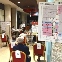 People wait to get vaccinated against COVID-19 at a mass inoculation site at a shopping mall in the city of Fukui in June. | KYODO
