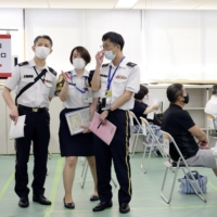 Self-Defense Force members work at a state-run mass vaccination site in Tokyo on June 9. The SDF will extend the opening period for the venues it operates in Tokyo and Osaka for about a month until late September, sources said Sunday. | POOL / VIA REUTERS