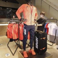 A worker at an Asics Corp. store in Osaka organizes items in a special section for the Tokyo Olympics and Paralympics.   KYODO
