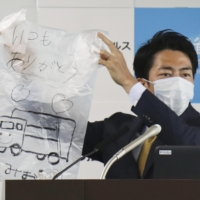 Environment Minister Shinjiro Koizumi appeals to people to write a thank you message to garbage collectors on trash bags in April 2020.   KYODO