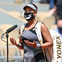 Naomi Osaka speaks to reporters during the French Open in Paris in May. The tennis star later withdrew from the tournament, citing mental health issues.  | Anadolu Agency / Getty / Kyodo