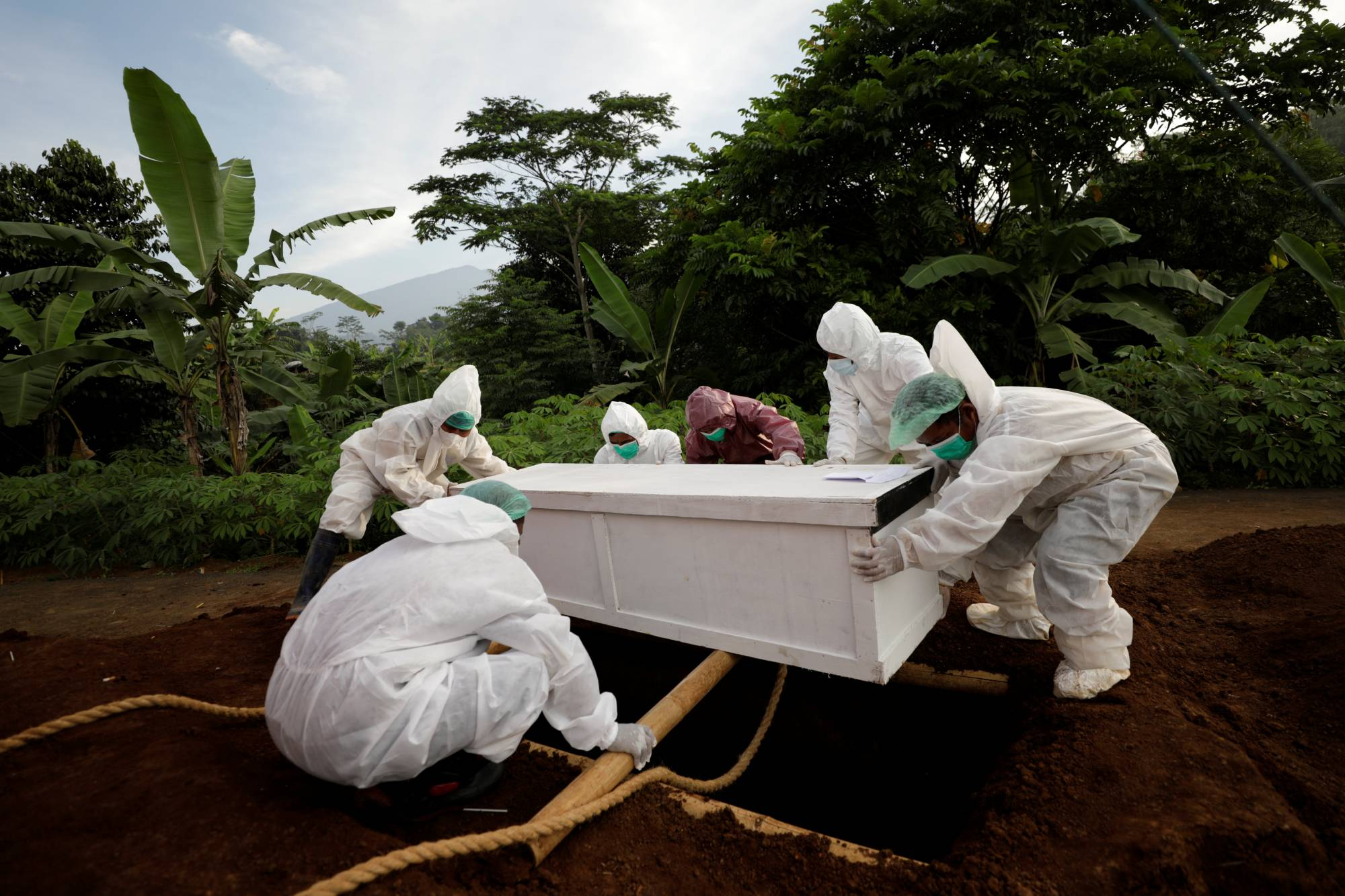 A person who died from COVID-19 complications is laid to rest in Bogor, West Java province, Indonesia, on July 8. The country, like others in the region, is struggling to cope with a devastating wave of cases driven by the highly contagious delta variant. |  REUTERS