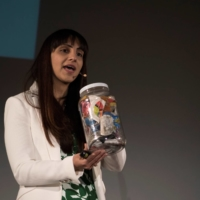 Priyanka Bakaya, founder of Renewlogy, holds a jar of mixed recyclables as she speaks at the 2015 TEDx Amherst event at the University of Massachusetts in April 2015.   CADE BELISLE / THE MASSACHUSETTS DAILY COLLEGIAN / VIA REUTERS