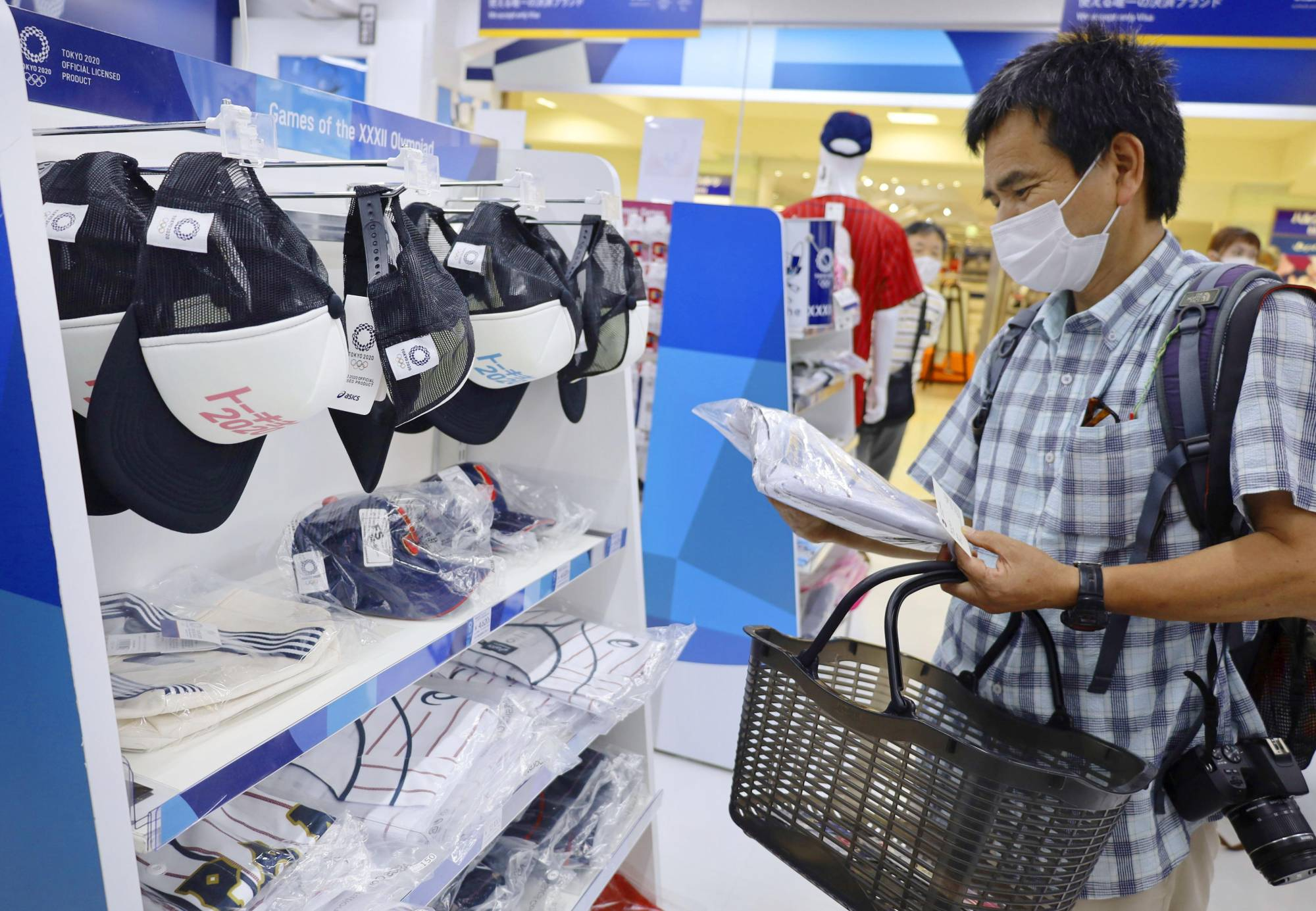 A man picks up a t-shirt at an official Olympics merchandise shop in Tokyo on July 26. | KYODO