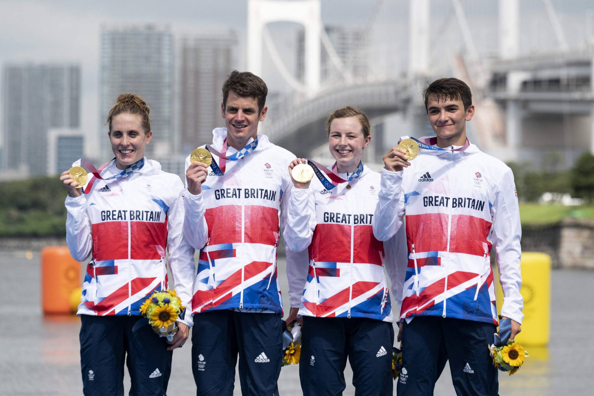 Britain's Alex Yee (left to right), Georgia Taylor-Brown Jessica Learmonth and Jonathan Brownlee pose on the podium during an Olympic medal ceremony after competing in the mixed-relay triathlon competition at Odaiba Marine Park in Tokyo on Saturday. | AFP-JIJI