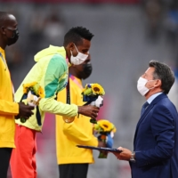 World Athletics chief Sebastian Coe presents men's 10,000-meter Olympic gold medalist Selemon Barega of Ethiopia with a bouquet flowers at Tokyo's National Stadium on Saturday.   REUTERS