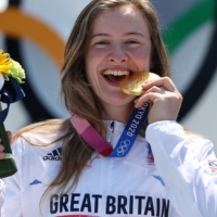 Gold medalist Charlotte Worthington of Britain takes a bite of her gold medal from the women's BMX freestyle event.  | REUTERS