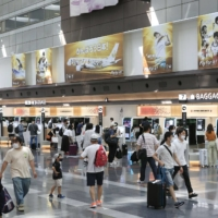 The departure lobby of Tokyo's Haneda Airport is filled with people on July 22, the first day of a four-day holiday. | KYODO
