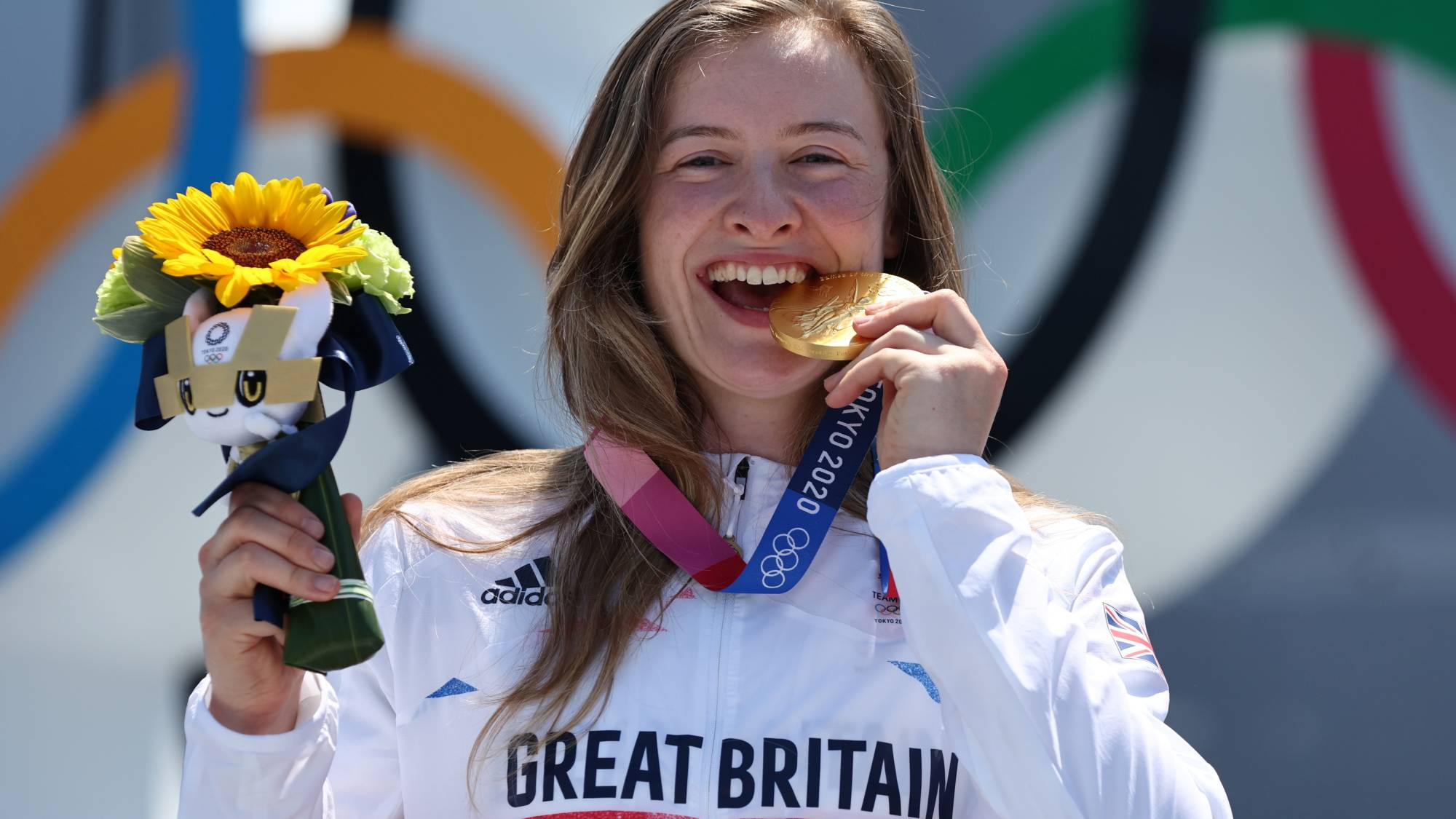 Gold medalist Charlotte Worthington of Britain takes a bite of her gold medal from the women's BMX freestyle event.   REUTERS