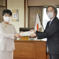 Justice Minister Yoko Kamikawa (left) receives a ministry committee report on changes to penal code articles concerning sex crimes on May 21.   KYODO