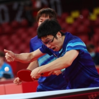 Japan's Jun Mizutani (front) and Koki Niwa take part in a match against Australia's Heming Hu and Xin Yan during the men's team table tennis competition at the Metropolitan Gymnasium in Tokyo on Monday. | REUTERS
