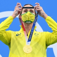 Olympic gold medalist Emma McKeon of Australia puts on her medal after the final of the women's 50-meter freestyle swimming event at the Tokyo Aquatics Centre on Sunday. | AFP-JIJI