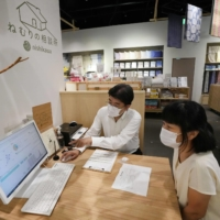 A woman visits a sleep consultation clinic in Tokyo, where she receives advice from a 'sleep master' on how to resolve her sleeping issues. | KYODO