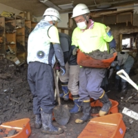 Volunteers clear mud Sunday inside a building in the area where entry restrictions were lifted in Atami, Shizuoka Prefecture, following the July 3 mudslide. | KYODO